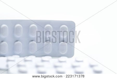 Macro shot detail of tablets pill in white blister pack for light resistance packaging isolated on white background. Medicine for treatment NCDs. Elderly people disease.