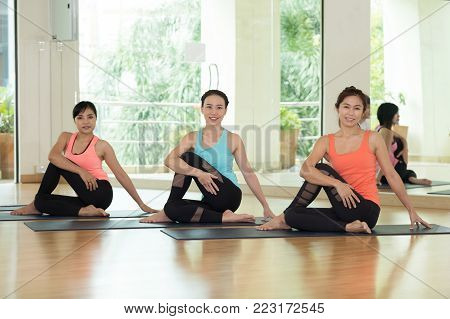 Group of asian women practicing yoga, fitness stretching flexibility pose, working out, healthy lifestyle, wellness, well being