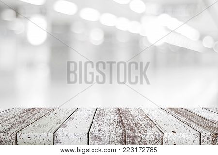 Empty vintage white wood table over blur store background, perspective wooden board background for product and food display montage