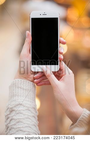 Beautiful female hands holding a mobile phone, indoor