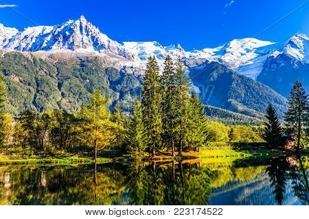 In the cold smooth water of the lake reflect the snow-capped mountain peaks of the Alps and the coniferous park. The mountain resort of Chamonix. Concept of active winter tourism