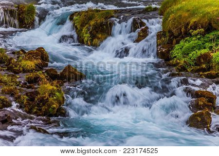 Boiling and rumbling cascading waterfall. Wide picturesque valley in Iceland. Concept of active and extreme tourism