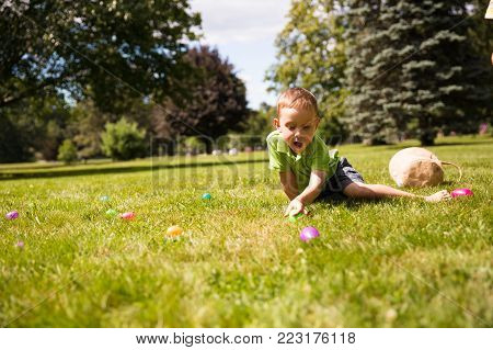 boy hunting for Easter eggs hidden in the grass. happy kid pick up colorful eggs. The concept of Easter Egg Hunt. copy space for your text