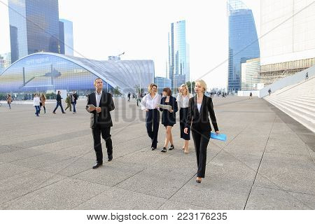 Employees of financial organization walking in   with tablet and document cases in  . Concept of prosperous team members and time management. Successful people wears business clothes.