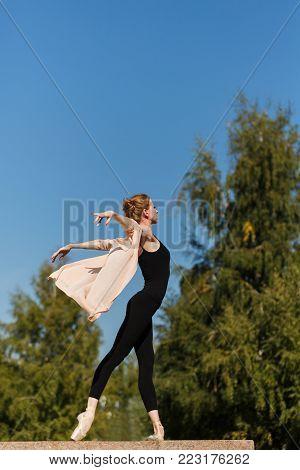 Slender ballerina in pointe dancing in the street. Performance in the city park. The art of dance. Slender female feet. Classical ballet.