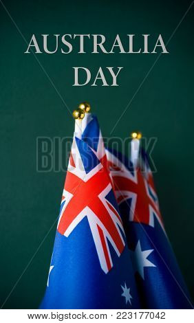 closeup of some australian flags and the text australia day against a dark green background