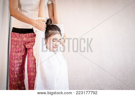 Woman is getting  her arm and back stretched in Thai massage