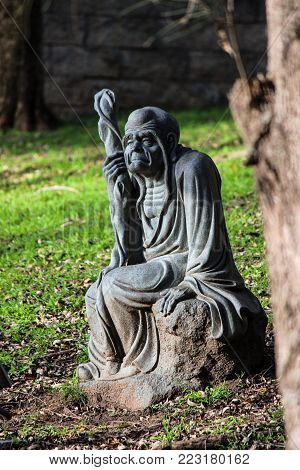 Wollongong, Nsw / Australia - July 8, 2015: Statue Of An Old Man, Sitting On A Rock In The Garden Of