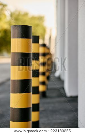 Closeup of yellow and black steel bollards that restrict movement of cars