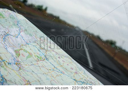 Close up of a map on a dash board looking through the windshield on a rainy road trip.
