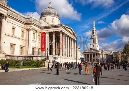 LONDON, UK - NOVEMBER 5, 2012: tourists and Londoners enjoying warm sunny autumn day on the Trafalgar Square in front of the National Gallery. The St. Martin-in-the-Fields church is seen in background