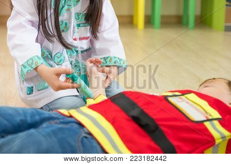 Two kid dress up to fireman and doctor at roll play classroom,Kindergarten preschool education concept.