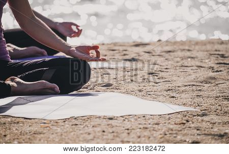 Close up hands of yoga master seated doing Hand Mudra and meditates on beach at coastline, Calm and relax concept,wellness and healthy lifestyle