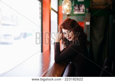 Portrait of beautiful redhead young girl with red lipstick. Concept person for a glossy magazine, model, eyes closed