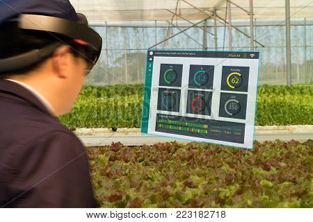 iot smart industry robot 4.0 agriculture concept,agronomist,farmer(blurred) using smart glasses (augmented mixed virtual reality,artificial intelligence technology) to monitoring  autonomous robotics condition