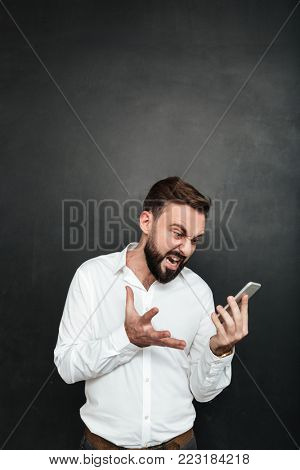 Studio photo of angry man yelling being irritated while looking on smartphone in his hand over dark gray background