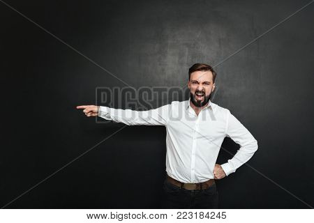 Picture of angry male employer screaming in outrage and pointing finger at door to get out over dark gray background