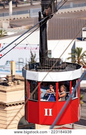 15 September 2011 Barcelona, Spain: Group of tourists in the red cable car on cable-way above the city of Barcelona