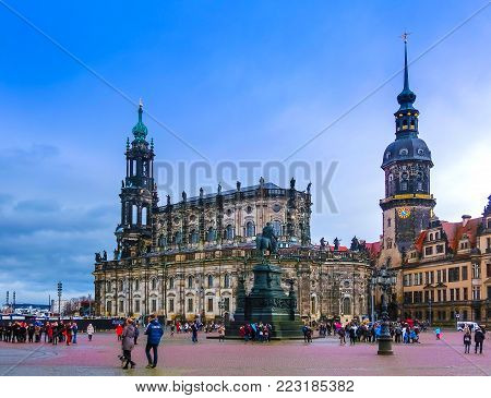 Dresden, Germany - December 31, 2017: The people going near Monument to King John of Saxony, Catholic Church and Dresden Castle, Dresden, Germany