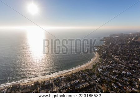 Aerial view of afternoon sun and pacific ocean fog above scenic Laguna Beach on the Orange County California coast.