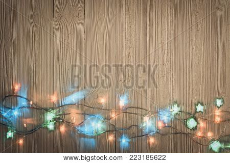 Fancy blinker light bulbs or garlands and wreath on wood table for Christmas or New years decoration background, space for add text or picture.