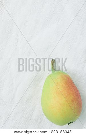 Simple Flat Lay of Single Ripe Organic Pear in Pastel Green Yellow Red Colors on Linen Fabric. Elegant Minimalist Japanese Style. Creative Image for Social Media Blog Product Branding. Copy Space