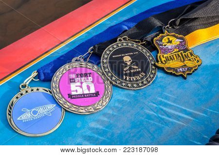 Fort Collins, CO, USA - January 6, 2018: A medal collection on the deck of a stand up paddleboard - awards for finishing 4 long distance river paddling races in 2017.