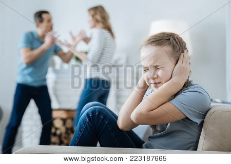 Poor child. Miserable fair-haired little girl closing her ears and sitting on the sofa while her parents quarrelling