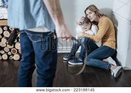 Terrified miserable fair-haired mother and girl sitting in the corner and mom hugging her daughter while daddy holding a belt and a bottle