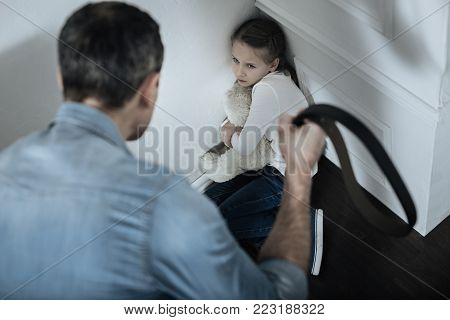 Aggressive. Frightened miserable fair-haired girl sitting in the corner and hugging a teddy bear while daddy holding a belt