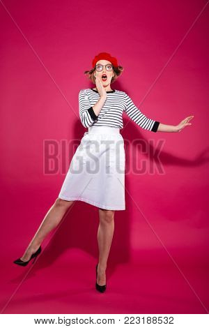 Full length image of Shocked ginger woman in eyeglasses holding cheek and looking at the camera over pink background