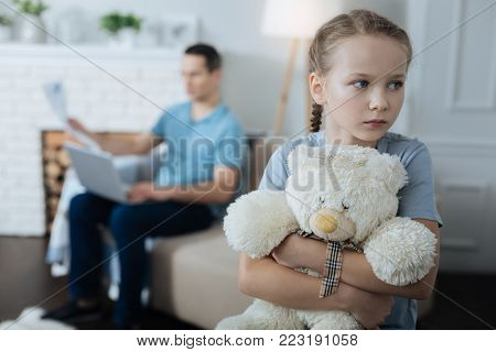 Loneliness. Sad blue-eyed fair-haired little girl holding her toy and standing in the room while her daddy working in the background