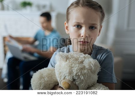 Miserable. Unhappy blue-eyed fair-haired little girl holding her toy and standing in the room while her daddy working in the background