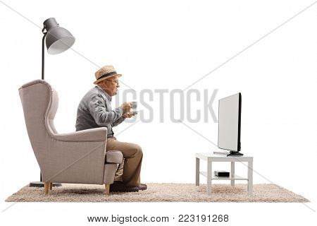 Mature man with a cup sitting in an armchair and watching television isolated on white background