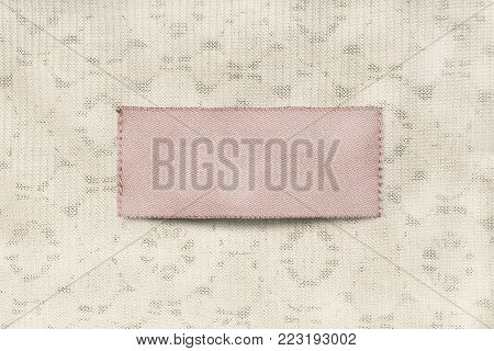 Blank pink textile clothes label on beige textile background closeup
