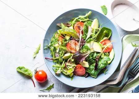 Fresh green salad with mixed green leaves, tomatoes and avocado with yogurt sauce. Clean eating and diet food.