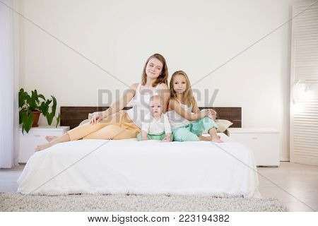 three girls play sisters in the morning on the bed in the bedroom