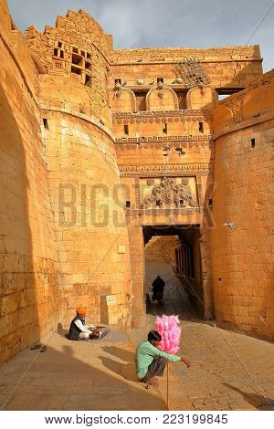 JAISALMER, RAJASTHAN, INDIA - DECEMBER 21, 2017: The entry Gate Suraj Pol to Jaisalmer Fort with a musician and a street seller in the foreground