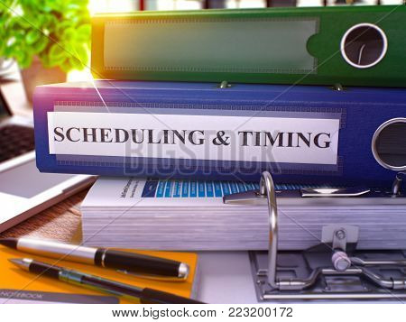 Blue Ring Binder with Inscription Scheduling and Timing on Background of Working Table with Office Supplies and Laptop. Scheduling and Timing Business Concept on Blurred Background. 3D Render.