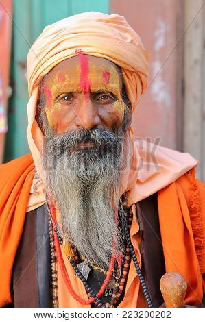 BIKANER, RAJASTHAN, INDIA - DECEMBER 23, 2017: Portrait of a Sadhu (holy man) with a long beard and colorfully dressed