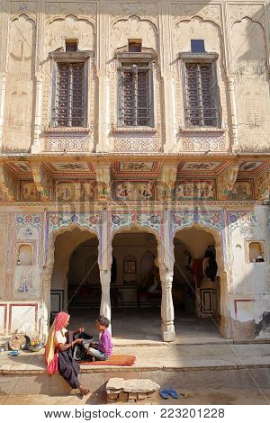 MANDAWA, RAJASTHAN, INDIA - DECEMBER 27, 2017: Chokani Double Haveli with frescoes and a woman with her child in the foreground