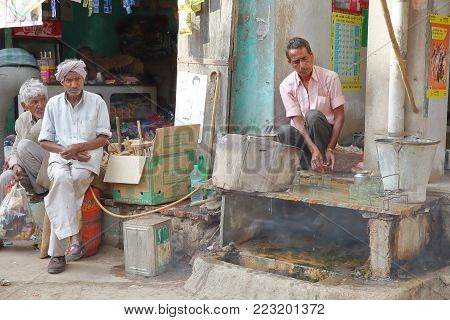 MANDAWA, RAJASTHAN, INDIA - DECEMBER 27, 2017: Street scene with a shopkeeper preparing Masala Chai in a traditional stall with local customers