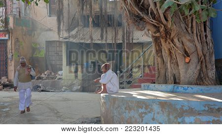 NAWALGARH, RAJASTHAN, INDIA - DECEMBER 28, 2017: Street scene early morning with a man dressed in white sitting in front of a Banyan Tree