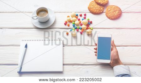 Above view of woman drinking coffee with smartphone in hand. Clipping path.