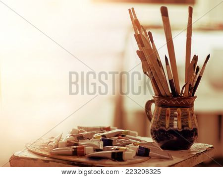 Paint brushes in art pot. Easel with oil and watercolor stack paints in morning sunlight dawn. Toning still life.