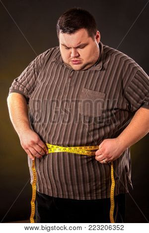 Man belly fat with tape measure weight loss around body on black background. First day of diet. Clothes for big people.