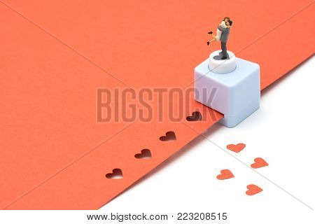 couple Miniature 2 people standing with Heart shaped punching machine Punch red paper Red heart is the promise of love.  as background Valentine concept with copy spaces for your text or design.