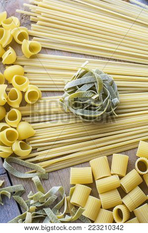 One piece of green pasta is on the yellow linguini