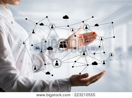 Business woman in shirt keeping black social media network structure in hands with office view on background. Mixed media.