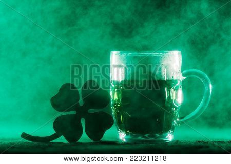 Beer mug with green beer in it and a four-leaf clover in a green smoke. Irish culture. St. Patrick's Day.